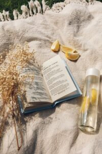 bottle with lemon water and a book