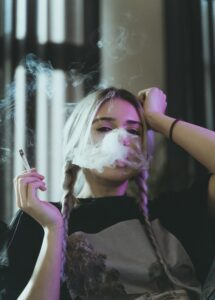girl holding a cigarette and smoking